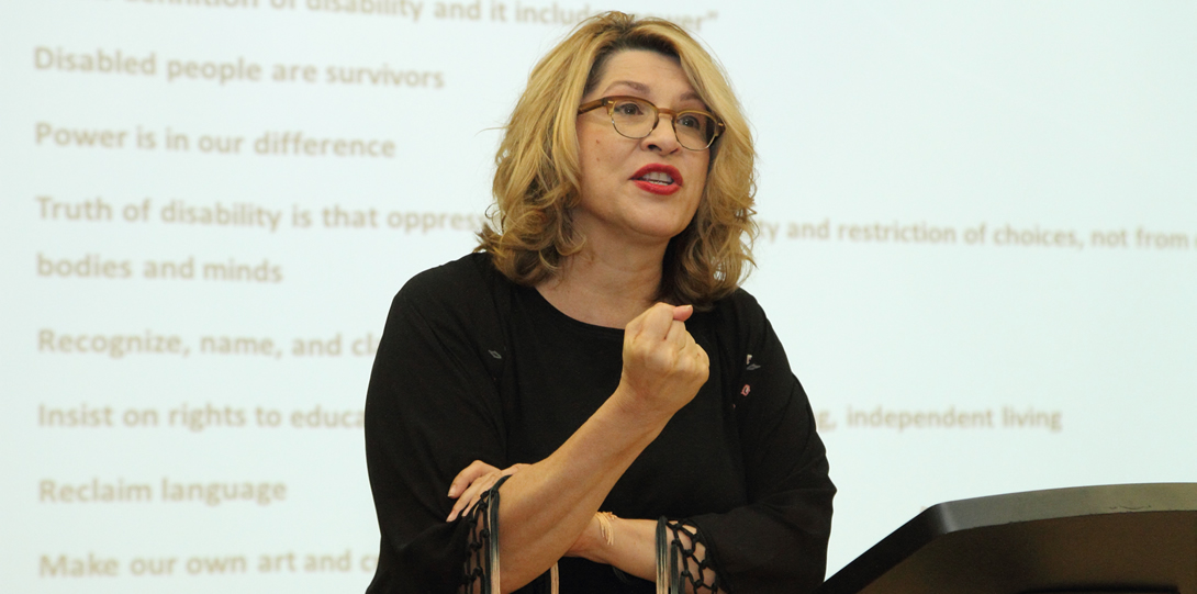 "A white woman wearing glasses, a black blouse, and red lipstick stands behind a podium. She clutches her right arm with her left hand and makes a fist with her right hand.  She stands in front of a screen with text that reads things such as ""Disabled people are survivors"", ""Power is in our difference"", and ""Reclaim language"" among other things."