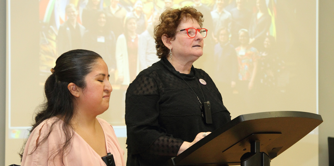 A Latina woman with a pink blouse and dark hair sits in front of a woman wearing a black blouse and red glasses stands behind a podium and address an audience.  The two woman are both in front of a screen with the DCC, LCC, and Erasing the Distance staffs.