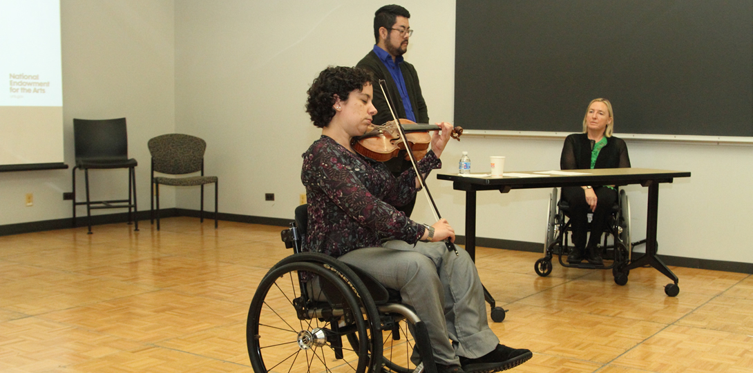 A woman using a wheelchair plays the violin in the foreground of the image. She has dark hair, is wearing a gray pants, and a multicolored blouse. A sign language interpreter stands behind her, and a white woman in a black and green blouse sits in a wheelchair along the wall.