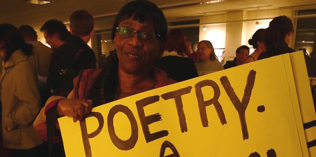 Disabled poet, dancer and activist Pennie Brinson at one of her poetry readings. An African-American woman with glasses holds a large yellow sign that reads
