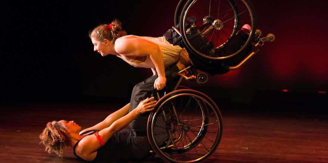 Disabled dancer Alice Shepherd and a partner performing at the yearly integrated dance show Counterbalance, which features dancers with and without disabilities. African American woman lying on her back in her wheelchair with her arms stretched forward. A white woman, who also uses a wheelchair, balances over the woman on her back. The two wheelchairs support one another as both woman face each other in a delicate balance.