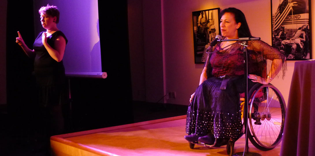 Disabled poet Maria Palacios, from the Disability Arts Performance organization Sins Invalid, performs one of her poems. A latina woman, with long black hair is seated in a wheelchair before a standing mic. She wears a black lace shawl with fringe over a beige sleeveless shirt and a long black skirt with rows of gold sequins stitched on the bottom. She places her left hand on her hip as she stares out to the audience. To her right is a sign language interpreter, interpreting her poetry performance in ASL.