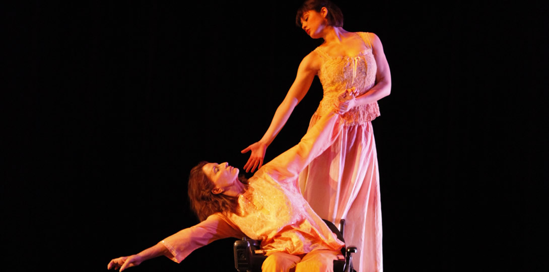Disabled dancer Ginger Lane, a member of Momenta Dance Company, performs an integrated dance piece with a partner. A white woman with shoulder length red hair sits in a wheelchair and tilts her body to the right side, while her right hand is outstretched. Her left hand is also outstretched and held by her partner, who stands upright on the back of the wheelchair. Her partner is a white woman with short black hair. She also leans to the right hand side, her arm and palm outstretched towards the wheelchair users upturned face. The wheelchair user wears a cream colored long sleeve tunic with white sequins sewn on the front and cream colored flowing pants. Her partner wears a sleeveless cream colored lace top and a flowing cream colored skirt.