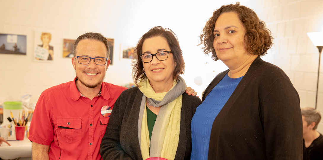 Dean Adams, Rosa Cabrera, Director of the Latino Cultural Center and Amalia Pallares, Associate Chancellor and Vice Provost for Diversity stand together smiling during the DCC Housewarming.