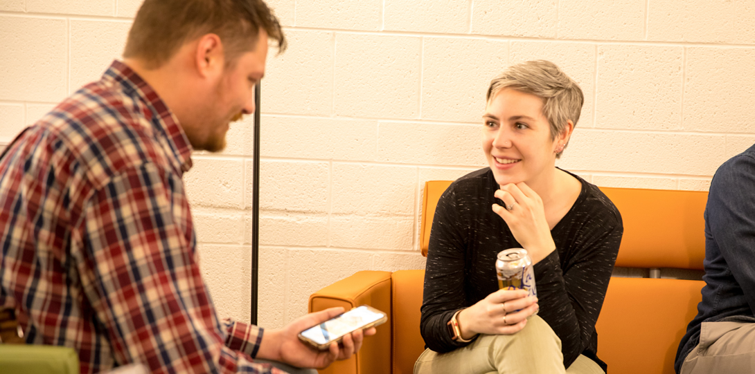 Nicole Sims, DRC Staff member, sits and smiles while talking to another student. Nicole is wearing a black shirt and light green pants, and is holding a drink. The other student is sitting and looking down at a phone.
