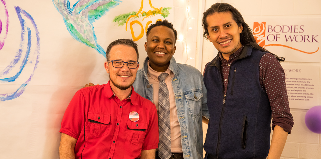 Dean Adams, Interim Director of DCC, JT Turner, Director of Gender and Sexuality Center (GSC), and Moises Villada, GSC Assistant Director stand together smiling in front of the hand painted mural during the DCC Housewarming.s.