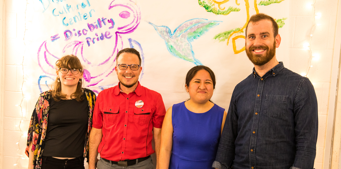"""DCC Staff - Sylvie Rosenkalt, Dean Adams, Lily Diego-Johnson, and Brian Heyburn, stand smiling in front of the collaborative, hand-painted mural during the DCC Housewarming on April 18th, 2019. The Mural behind them reads: """"Disability Cultural Center = Disability Pride"""", which is surrounded by a curvy design in purple and blue paint. To the right of this design is a bird painted in blue and green paint, and to the far right of the image, a tree is painted in green and orange paint,; under which is written, """"DCC"""""""