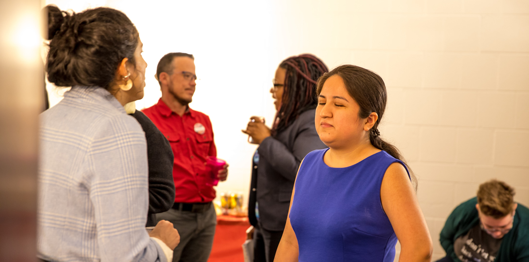 Lily Diego-Johnson, Program Coordinator of DCC stands facing towards the camera as she speaks to Sophia Hamilton, Director of the Disability Resource Center.