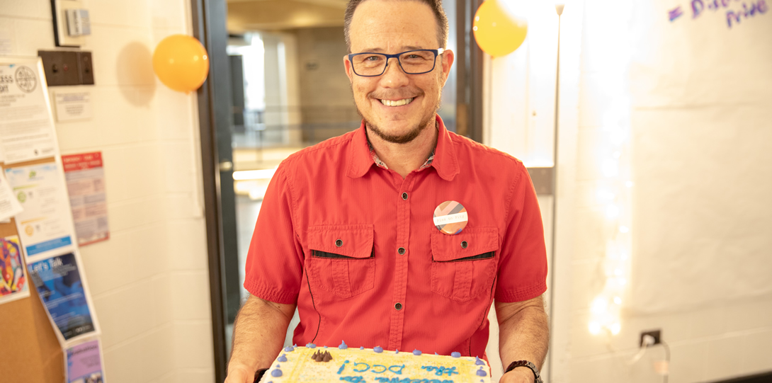 """Dean Adams, Interim Director, stands smiling at the camera holding a cake. The cake reads """"Welcome to the DCC"""" in blue icing. He is wearing a read shirt and a pin that says """"Piss on Pity"""". Balloons are in the background."""