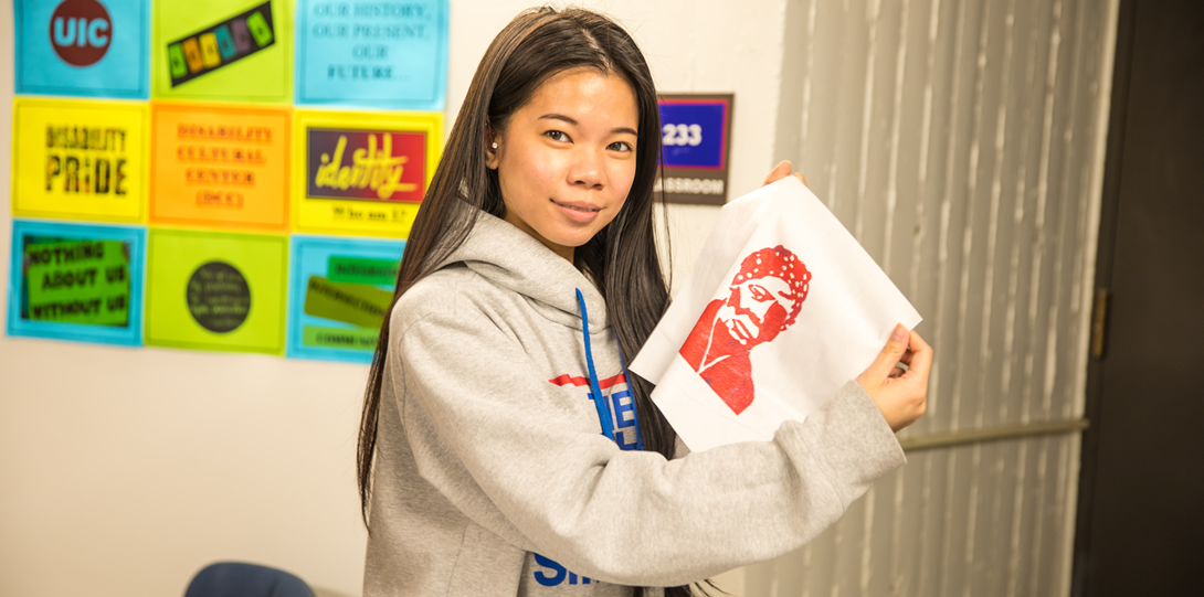 """An Asian-American student in a sweatshirt holds a bright red Harriet Tubman print that she made up for the camera. She is smiling. In the background there is a sign that is blurred but the words """"UIC"""" """"Identity"""" """"Disability Pride"""" and """"Nothing About Us Without Us"""" can be made out."""