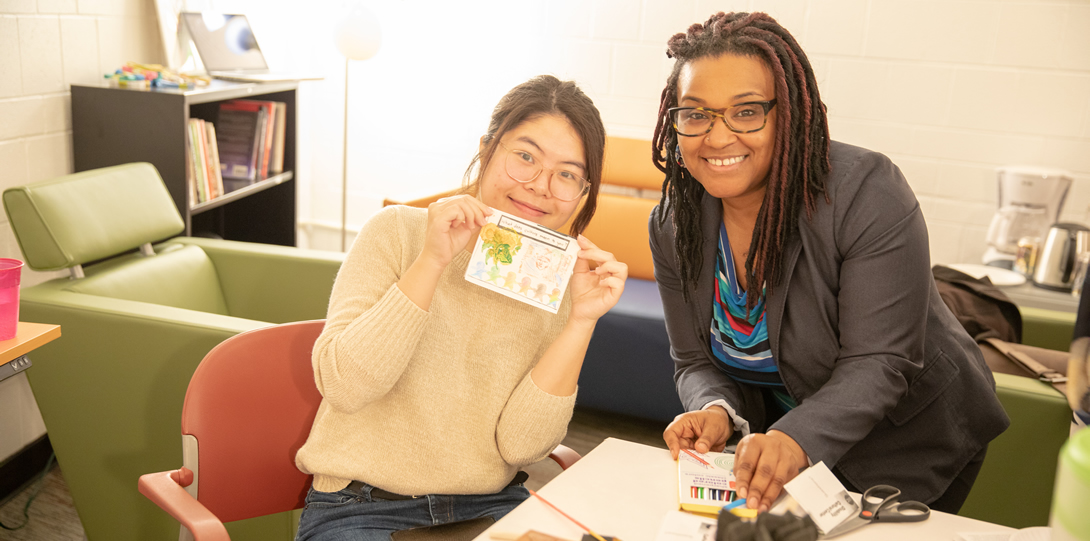 An Asian-American student and Alana Gunn, faculty, member look at the camera. One is sitting at the table and the other leans in smiling to join the photo. They are both smiling. One is holding up a zine page covered with stamps. At the table in front of them there are stamps, paints, colored pencils in the foreground. In the background there are green armchairs and a bookshelf and lamp.