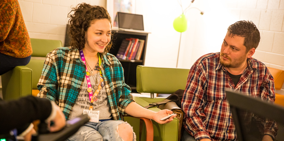 Allyson Nolde, Graduate Assistant at the Gender and Sexuality Center, and Evan Reynolds, Graduate Student, sit speaking to a small group. Both Allyson and Evan are wearing plaid shirts. Allyson is wearing a rainbow colored lanyard with her name tag attached. She is smiling while Evan looks on.