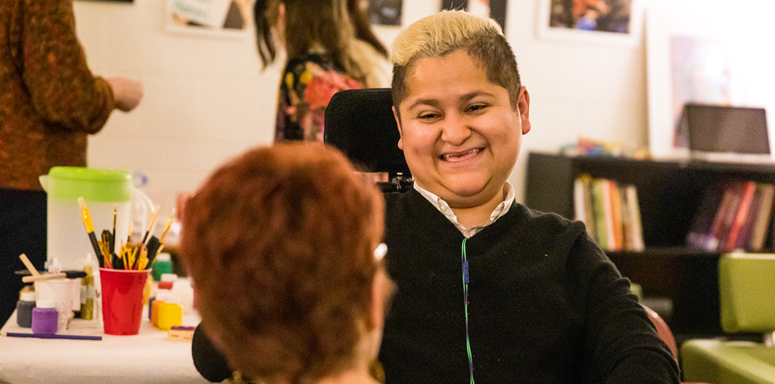 Hugo Travino, Disability Specialist at the Disability Resource Center, smiles while talking to Liat Ben-Moshe, Assistant Professor in Criminology, Law, and Justice. Hugo is facing directly towards the camera while looking at Liat. Liat has her back towards the camera and is in the foreground. Other people stand in the background around a table with art supplies.