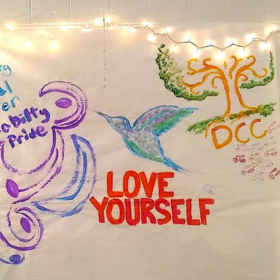 DCC mural spring 2019, handpainted with a tree, hummingbird, and swirls. Large letters read