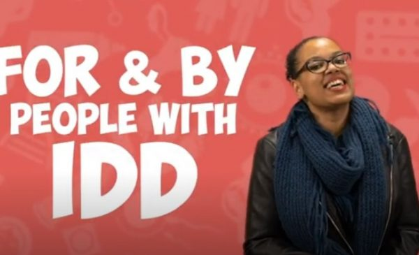A smiling Black woman in front of a red background with white words that say